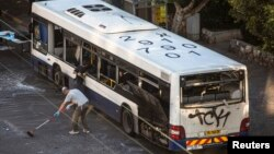 Israeli police explosive experts survey a damaged bus at the scene of an explosion in a Tel Aviv suburb Dec. 22, 2013.