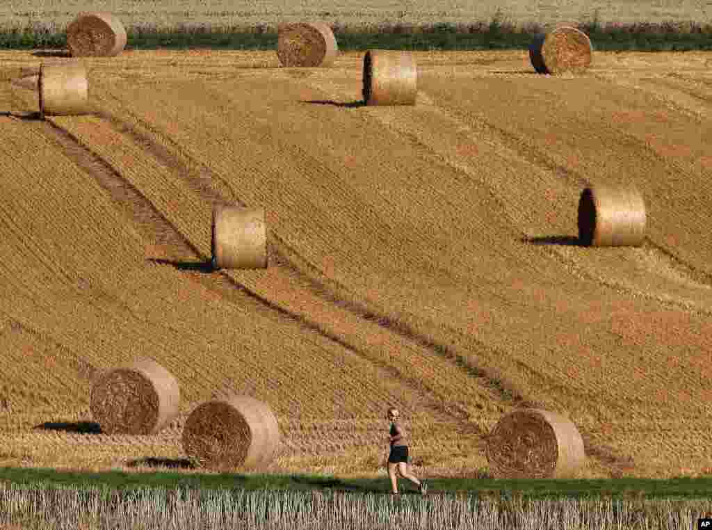 A woman runs by rolls of straw on a field in Frankfurt, Germany.