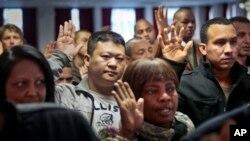 Inmigrantes alzan su mano para prestar juramento como nuevos ciudadanos estadounidenses en Nueva York.
