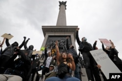 Activists, some wearing face coverings or face masks as a precautionary measure against COVID-19, hold placards as they attend a Black Lives Matter protest at Nelson's Column in Trafalgar Square in London on June 12, 2020.