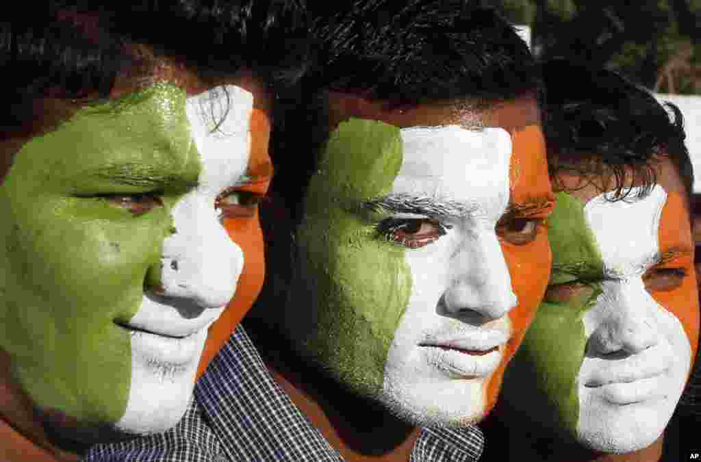 Indian cricket fans with their faces painted with the colors of the Indian flag, wait to enter the Sardar Patel Stadium, venue of the second Twenty20 cricket match between India and Pakistan, in Ahmadabad, India, December 28, 2012.
