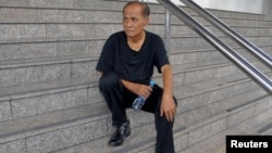 Chalad Vorachat, a retired navy lieutenant and serial hunger striker, sits on the steps of the criminal court in Bangkok, June 10, 2014.