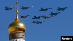 Military jets fly over an Orthodox Christian church during a rehearsal for the Victory Day parade in Moscow, May 7, 2013.