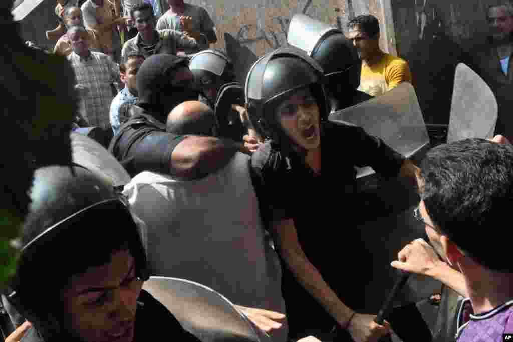 8月17日,埃及安全部队护送一名抗议者走出法塔赫清真寺,经过气愤的人群。此前,在开罗市中心的拉姆西斯广场附近爆发了激烈的巷战,数十人死亡。