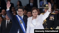 Honduras' President Juan Orlando Hernandez, left, and his wife Ana Rosalinda wave after his swearing in ceremony as new president in Tegucigalpa, Honduras, Jan. 27, 2014.