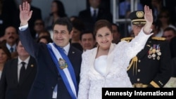 FILE - Honduras' President Juan Orlando Hernandez, left, and his wife Ana Rosalinda wave after his swearing in ceremony as new president in Tegucigalpa, Honduras, Jan. 27, 2014.