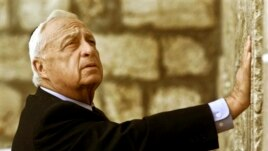 FILE - Ariel Sharon, Israel's then-Prime Minister-elect, touches Judaism's holiest site, the Western Wall, Jerusalem, Feb. 7, 2001.