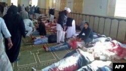 Des Égyptiens passent devant des corps après une attaque à la bombe à la mosquée de Rawda, à l'ouest de El-Arish, capitale du nord du Sinaï, 24 novembre 2017.