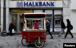 FILE - A street vendor sells roasted chestnuts in front of a branch of Halkbank in central Istanbul, Turkey.