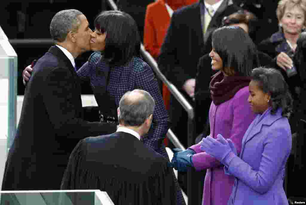 U.S. President Barack Obama (L) is kissed by first lady Michelle Obama after being sworn in by Supreme Court Justice John Roberts during inauguration ceremonies in Washington, January 21, 2013. Sasha and Malia Obama applaud at right.