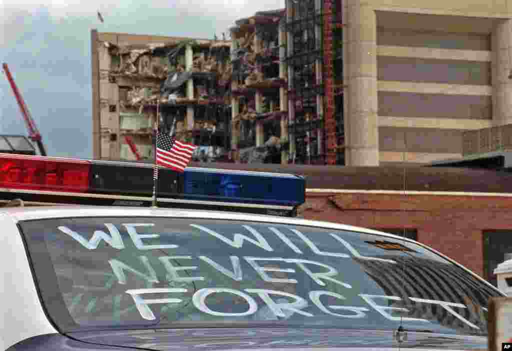 """FILE - In this April 24, 1995 file photo, an Oklahoma City police car decorated with the words, """"We will never forget,"""" and a small American flag sits near the Alfred P. Murrah Federal Building in Oklahoma City."""