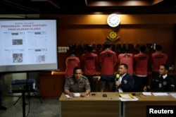 National Police Cyber Crime Director Brig. Gen. Fadil Imran (C), gestures in front of suspects arrested for cyber-crime related hoaxes on social media during a press conference in Jakarta, Indonesia, Feb. 28, 2018.