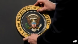 FILE - The Presidential Seal is placed on a podium in preparation for a presidential speech. With members of President Donald Trump's inner circle under investigation for possible Russia ties, questions are being asked whether, theoretically and practically, a sitting U.S. president could be charged with a crime.