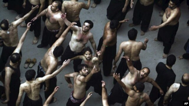 Iraqi Shi'ite Muslim men beat themselves with their hands during a Muharram procession to mark Ashura in Kerbala, about 80 km (50 miles) southwest of Baghdad, Dec 2010