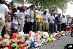 Keluarga, teman dan para warga mengheningkan cipta bagi Michael Brown, Minggu (8/8) di Ferguson, Missouri.