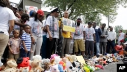 Family, friends and supporters pause for a moment of silence at a memorial to Michael Brown, Sunday, Aug. 9, 2015, in Ferguson, Missouri.