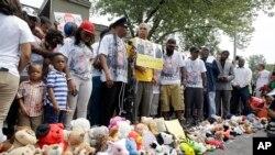 Warga kota Ferguson, Missouri mengheningkan cipta untuk mengenang kematian Michael Brown, dalam pawai hari Minggu (9/8).