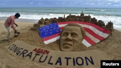 Patnaik, an Indian artist gives finishing touches to a sand sculpture of U.S. President Obama on a beach in Puri, India.