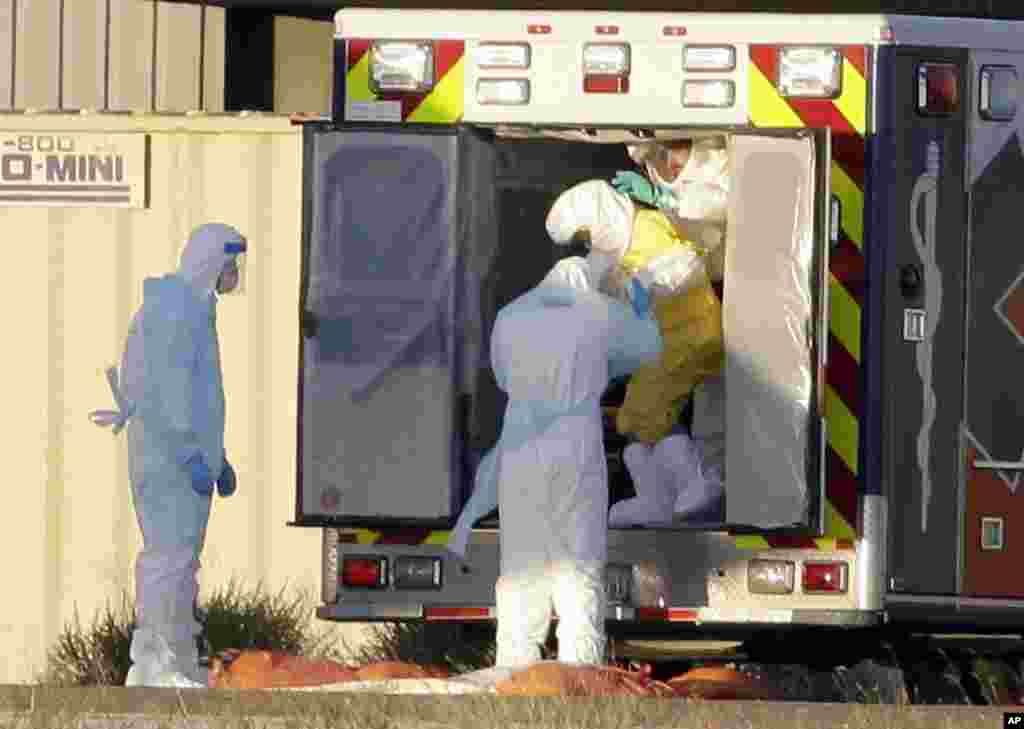 Medical staff in protective gear escort Nina Pham, exiting the ambulance, to a nearby aircraft at Love Field, Dallas, Oct. 16, 2014.