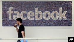 In this March 15, 2013, photo, a Facebook employee walks past a sign at Facebook headquarters in Menlo Park, Calif.