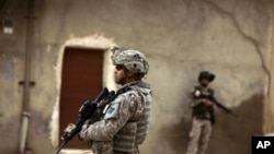 An Iraqi Army soldier and a U.S. Army soldiers from Delta Co., 1st Combined Arms Battalion, 67th Armor Regiment stand guard during a joint patrol in Mosul, Iraq, March 2009 (file photo)