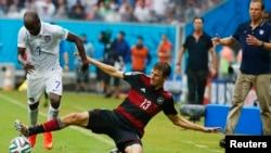 Pemain AS DaMarcus Beasley (kiri) berebut bola dengan pemain Jerman Thomas Mueller, sementara pelatih AS Juergen Klinsmann (kanan) menyaksikan dari pinggir lapangan di kota Recife, Brazil (26/6).