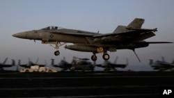 Jet tempur Koalisi AS untuk serangan terhadap ISIS mendarat di atas kapal di Teluk Persia, setelah terbang dari Irak. (AP/Hasan Jamali)