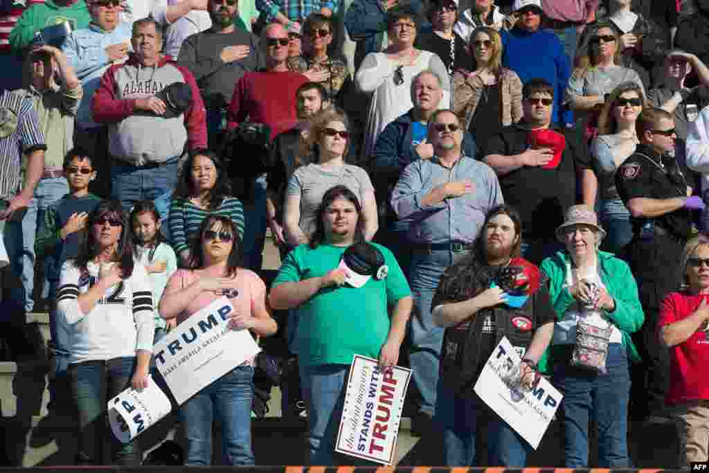 Guests listen to the national anthem during a campaign rally for Republican presidential candidate Donald Trump at the Madison City Schools Stadium in Madison, Alabama, Feb. 28, 2016.