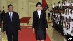 Cambodia's Prime Minister Hun Sen, left, walks together with Thai counterpart Yingluck Shinawatra, center, as she reviews an honor guard inside the Peace Palace in Phnom Penh.
