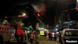 Karyawan dan para tamu hotel yang dievakuasi dari lokasi kejadian, berdiri di jalanan dan mengamati kepulan asap kebakaran dari bangunan Resorts World di Pasay City, Metro Manila, FIlipina, 2 Juni 2017.