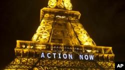 """La Tour Eiffel allume avec le slogan « Passons à l'action """", se référant à la COP21 , la Conférence des Nations Unies sur les changements climatiques à Paris , le dimanche 6 décembre 2015 ."""