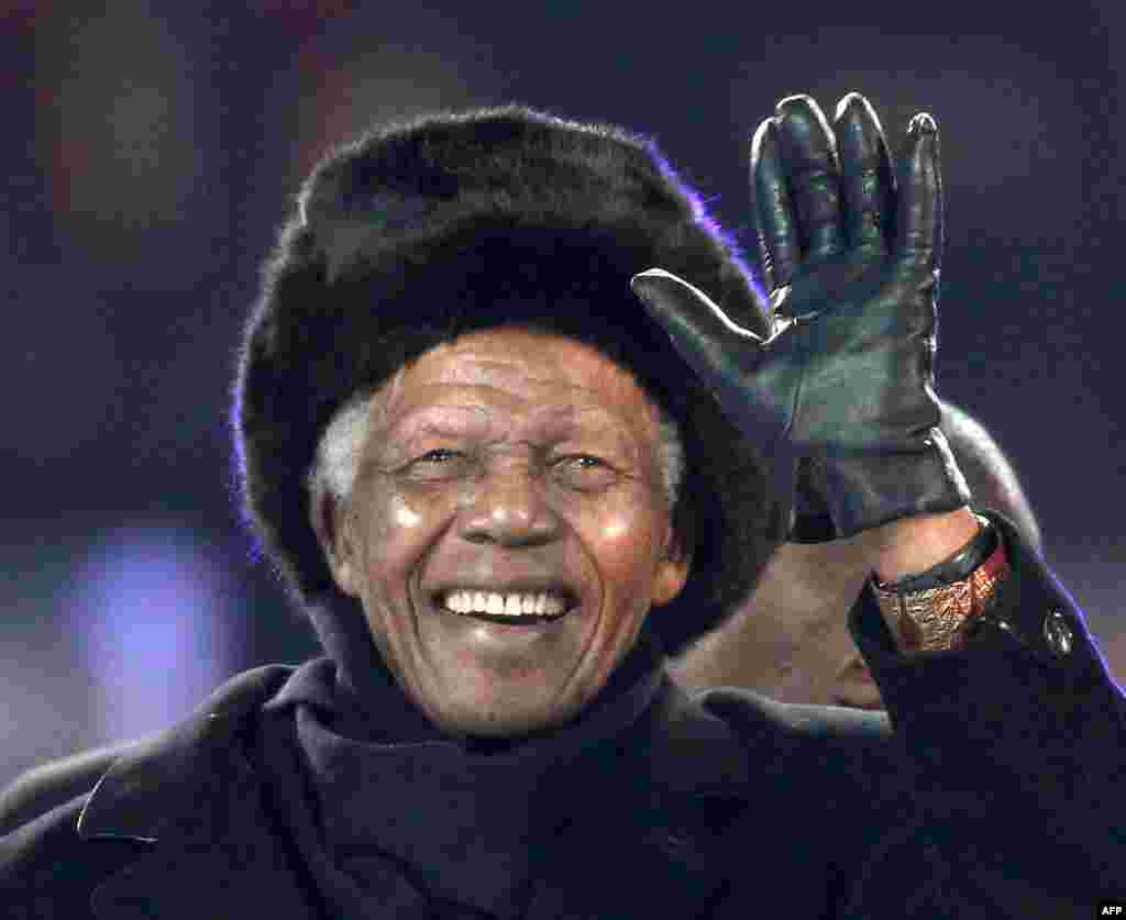 Nelson Mandela waves as he arrives to attend the 2010 World Cup football final Netherlands vs. Spain on July 11, 2010 at Soccer City stadium in Soweto.