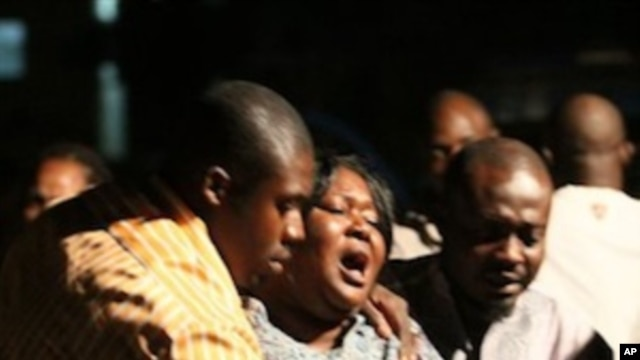 A woman who lost a relative in a bomb explosion, center, mourns at the Asokoro General Hospital, Abuja, Nigeria, 31 Dec 2010