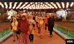 Pengurus kelenteng Xie Tian Gong, Sugiri Kustedja (kanan) berjalan di depan kelenteng bersama para peserta tur malam Imlek, Selasa (5/2/2019) malam. (VOA/Rio Tuasikal)
