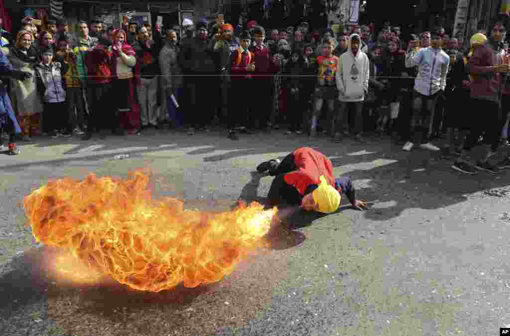 An Indian Sikh warrior blows fire as he demonstrations traditional martial art skills during a religious march.