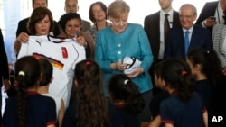 German Chancellor Angela Merkel (C) distributes shirts of the German national soccer team to Lebanese and Syrian displaced students studying together, during her visit to a Lebanese public school, in Beirut, Lebanon, June 22, 2018.