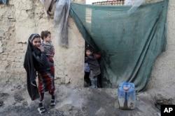 Seorang bocah laki-laki yang mengungsi mengintip melalui tirai rumah sementara di kota Kabul, Afghanistan, Rabu, 30 Desember 2020. (Foto: AP)