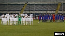 Players of the U.S. (in white) and of Ukraine (in blue) observe a minute of silence as a tribute to those who lost their lives in Kyiv during recent protests, before their international friendly soccer match in Larnaca, Cyprus, March 5, 2014.