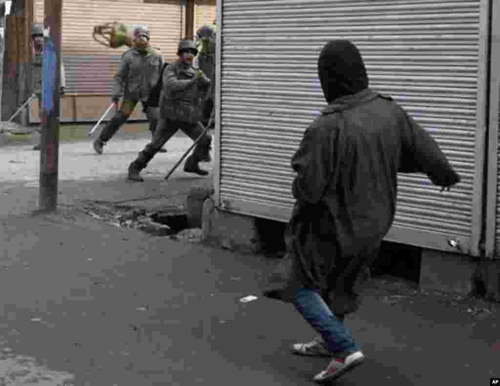 """A Kashmiri protester throws a """"kangri"""" or Kashmiri traditional firepot towards Indian police during a protest in Srinagar January 21, 2012. The protest was organised by separatist group, Jammu Kashmir Liberation Front (JKLF), to mark the anniversary of th"""