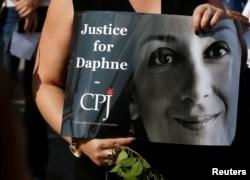 지난 10월 몰타에서 비드니자에서 열린 언론인보호위원회(Committee to Protect Journalists ·CPJ) 행사에서 한 참석자가 피살된 기자의 사진을 들고 있다.