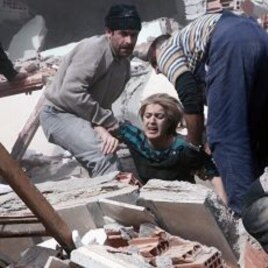 People rescue a woman trapped under debris after a powerful 7.2-magnitude earthquake struck eastern Turkey, collapsing about 45 buildings in Van province,October 23, 2011.