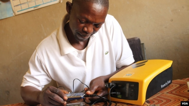 Michael Mugerwa uses his solar system to charge phones in Kiwumu, Uganda, Feb. 28, 2014. (Hilary Heuler/VOA)
