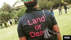 """Una donna attivista al raduno sport una maglietta con la """"Terra o Morte"""" lo slogan reprentative della posizione intransigente presa da attivisti ridistribuzione della terra. (A. Powell / VOA)"""