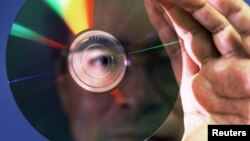 An August 26, 1999 of a Japanese researcher showing a 200-gigabyte memory disc, jointly developed by National Institute for Advanced Interdisciplinary Research and Sharp Corp at the Japanese government's research center in Tsukuba,
