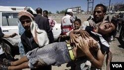Para demonstran mengangkat rekan mereka yang terluka dalam bentrokan dengan pasukan keamanan di ibukota Sana'a (15/10).