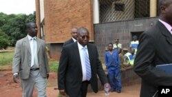 茨万吉拉伊内阁的能源电力发展部部长艾尔顿.曼戈马(中)3月11日在警察陪同下出现在哈拉雷的地方法庭外面