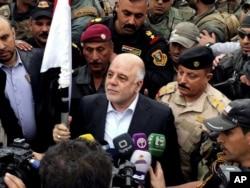 Thủ tướng Iraq Haider al-Abadi (giữa) giơ lá cờ Iraq tại thành phố Ramadi, 70 dặm (115 km) về phía tây Baghdad, sau khi thành phố này được tái chiếm bởi các lực lượng an ninh, ngày 29 tháng 12 năm 2015.