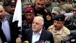 Le Premier Ministre Iranien Haider al-Abadi, au milieu, exhibe le drapeau irakien a Ramadi, 70 miles (115 kilometers) a l'Ouest de Baghdad, apres la reprise de la villa par les forces de securite, le 29 dec, 2015.