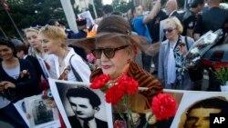 Žena nosi fotografije rodjaka ubijenih u Drugom svetskom ratu za vreme obeležavanja Dana pobede u Beogradu