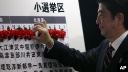 Japan's main opposition leader Shinzo Abe of the Liberal Democratic Party (LDP) marks on the name of one of those elected in parliamentary elections at the party headquarters in Tokyo, December 16, 2012.